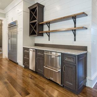 Wet bar - mid-sized farmhouse single-wall dark wood floor and brown floor wet bar idea in Atlanta with no sink, recessed-panel cabinets, dark wood cabinets, granite countertops, white backsplash and wood backsplash