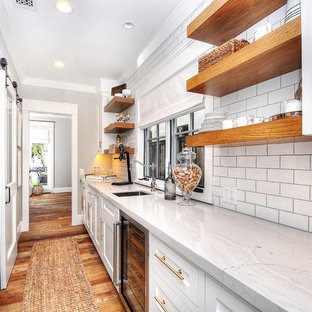 Home bar - cottage single-wall medium tone wood floor and brown floor home bar idea in Orange County with an undermount sink, beaded inset cabinets, white cabinets, white backsplash and subway tile backsplash