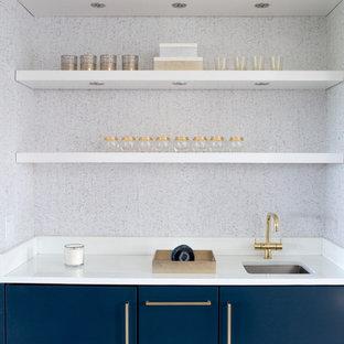 Ispirazione per un piccolo angolo bar con lavandino minimalista con lavello sottopiano, ante lisce, ante blu e top bianco