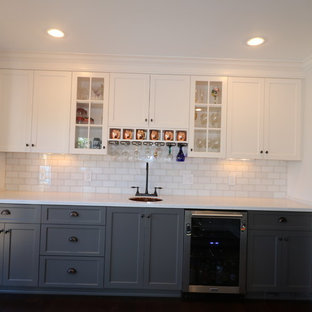 Inspiration for a medium sized traditional single-wall wet bar in Louisville with a submerged sink, recessed-panel cabinets, white cabinets, engineered stone countertops, white splashback, metro tiled splashback, medium hardwood flooring and brown floors.