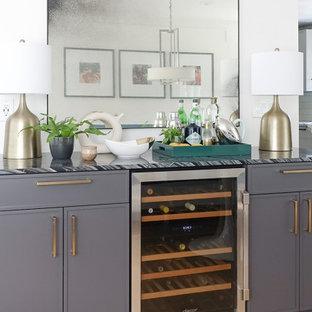 Immagine di un angolo bar senza lavandino minimalista di medie dimensioni con ante nere, top in marmo, parquet chiaro e top nero