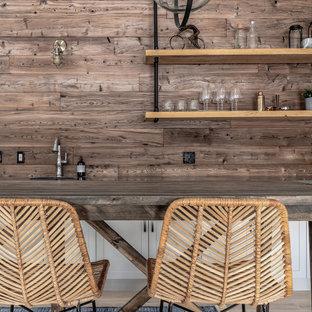 Idee per un grande angolo bar con lavandino classico con lavello sottopiano, ante in stile shaker, ante grigie, top in quarzo composito, paraspruzzi in legno, pavimento in laminato e top nero