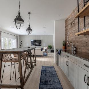 他の地域の広いトランジショナルスタイルのおしゃれなウェット バー (I型、アンダーカウンターシンク、シェーカースタイル扉のキャビネット、グレーのキャビネット、クオーツストーンカウンター、木材のキッチンパネル、ラミネートの床、黒いキッチンカウンター) の写真
