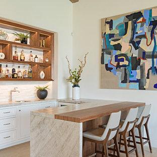 Esempio di un piccolo angolo bar con lavandino mediterraneo con lavello sottopiano, consolle stile comò, ante in legno scuro, top in quarzite, paraspruzzi bianco, paraspruzzi con piastrelle in pietra, pavimento in pietra calcarea, pavimento beige e top bianco