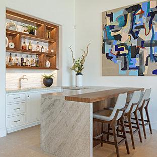 小さい地中海スタイルのおしゃれなウェット バー (コの字型、アンダーカウンターシンク、家具調キャビネット、中間色木目調キャビネット、珪岩カウンター、白いキッチンパネル、石タイルのキッチンパネル、ライムストーンの床、白いキッチンカウンター) の写真