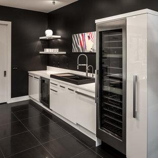 ミネアポリスの巨大なコンテンポラリースタイルのおしゃれなホームバー (ドロップインシンク、フラットパネル扉のキャビネット、白いキャビネット、クオーツストーンカウンター、白いキッチンパネル、磁器タイルの床、黒い床) の写真