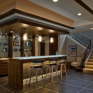 Immagine di un grande bancone bar design con ante lisce, ante marroni, top in vetro, paraspruzzi blu, paraspruzzi con piastrelle di vetro, pavimento in gres porcellanato, pavimento grigio e top blu