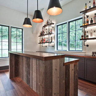 Example of a mid-sized urban l-shaped medium tone wood floor and brown floor wet bar design in Nashville with an undermount sink, shaker cabinets, gray cabinets, wood countertops and brown countertops
