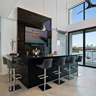 マイアミのコンテンポラリースタイルのおしゃれな着席型バー (L型、黒いキャビネット、茶色いキッチンパネル、ベージュの床、黒いキッチンカウンター) の写真