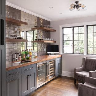 ニューヨークのトラディショナルスタイルのおしゃれなウェット バー (I型、アンダーカウンターシンク、落し込みパネル扉のキャビネット、グレーのキャビネット、木材カウンター、グレーのキッチンパネル、サブウェイタイルのキッチンパネル、濃色無垢フローリング、茶色い床、茶色いキッチンカウンター) の写真
