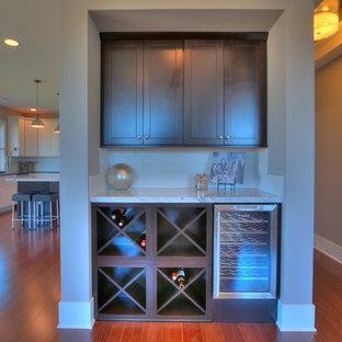 シアトルの小さいトランジショナルスタイルのおしゃれなホームバー (竹フローリング、ll型、フラットパネル扉のキャビネット、濃色木目調キャビネット、人工大理石カウンター、白いキッチンパネル、セラミックタイルのキッチンパネル、茶色い床) の写真