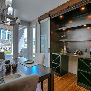 シアトルの中くらいのトランジショナルスタイルのおしゃれなウェット バー (竹フローリング、ll型、フラットパネル扉のキャビネット、ヴィンテージ仕上げキャビネット、木材カウンター、黒いキッチンパネル、茶色い床) の写真