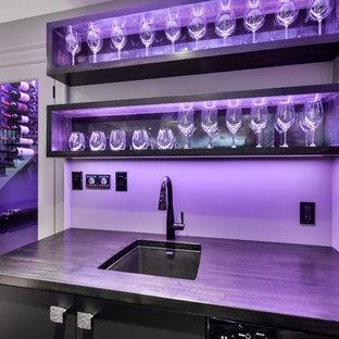 Immagine di un grande angolo bar con lavandino moderno con ante lisce, ante nere e top in legno