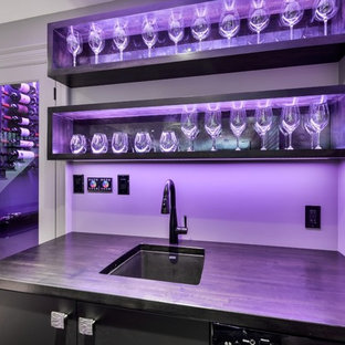 Inspiration for a large modern l-shaped wet bar in Toronto with flat-panel cabinets, black cabinets and wood worktops.