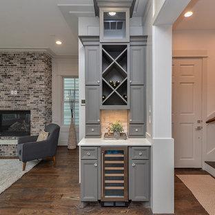 Modelo de bar en casa lineal, clásico, pequeño, sin pila, con armarios con paneles empotrados, puertas de armario grises, salpicadero blanco, suelo de madera oscura, suelo marrón y encimeras blancas