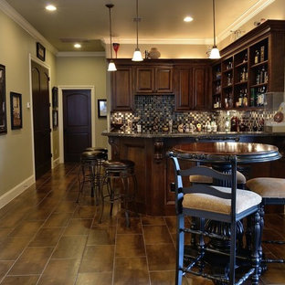 Example of a mid-sized classic l-shaped slate floor seated home bar design in Houston with an undermount sink, raised-panel cabinets, medium tone wood cabinets, granite countertops, multicolored backsplash and mosaic tile backsplash