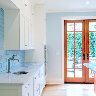 Design ideas for a large eclectic u-shaped wet bar in Seattle with a submerged sink, glass-front cabinets, white cabinets, marble worktops, blue splashback, metro tiled splashback, light hardwood flooring, brown floors and white worktops.