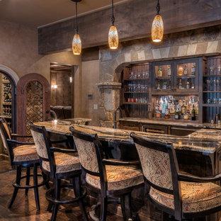 アトランタの広いラスティックスタイルのおしゃれなホームバー (ll型、レイズドパネル扉のキャビネット、濃色木目調キャビネット、濃色無垢フローリング、茶色い床、グレーのキッチンカウンター) の写真