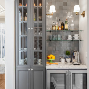 Example of a small eclectic single-wall medium tone wood floor and brown floor wet bar design in Seattle with recessed-panel cabinets, gray cabinets, quartzite countertops, gray backsplash, terra-cotta backsplash and white countertops