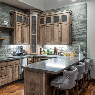 Mountain style u-shaped dark wood floor and brown floor seated home bar photo in Sacramento with an undermount sink, shaker cabinets, medium tone wood cabinets, gray backsplash and gray countertops