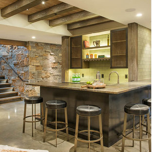 Inspiration for a mid-sized rustic l-shaped concrete floor and gray floor seated home bar remodel in Other with green backsplash, subway tile backsplash and glass-front cabinets
