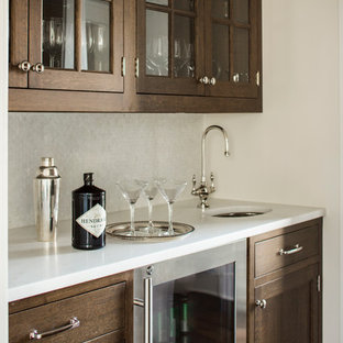 This is an example of a large classic galley wet bar in New York with a submerged sink, shaker cabinets, medium wood cabinets, marble worktops, beige splashback, mosaic tiled splashback and white worktops.