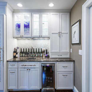 Small traditional single-wall wet bar in Cincinnati with a submerged sink, recessed-panel cabinets, white cabinets, white splashback and mosaic tiled splashback.