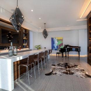 ロサンゼルスの中くらいのコンテンポラリースタイルのおしゃれなウェット バー (ll型、アンダーカウンターシンク、フラットパネル扉のキャビネット、グレーのキャビネット、クオーツストーンカウンター、茶色いキッチンパネル、木材のキッチンパネル、ライムストーンの床、グレーの床、白いキッチンカウンター) の写真