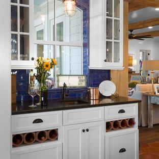 シャーロットのビーチスタイルのおしゃれなウェット バー (I型、アンダーカウンターシンク、ガラス扉のキャビネット、白いキャビネット、青いキッチンパネル、サブウェイタイルのキッチンパネル、テラコッタタイルの床、オレンジの床、黒いキッチンカウンター) の写真