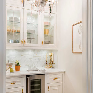 Elegant single-wall home bar photo in New York with glass-front cabinets, white cabinets, white backsplash and no sink