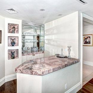 マイアミの中くらいのトラディショナルスタイルのおしゃれなウェット バー (ピンクのキッチンカウンター、I型、シンクなし、レイズドパネル扉のキャビネット、白いキャビネット、御影石カウンター、ミラータイルのキッチンパネル、濃色無垢フローリング、茶色い床) の写真