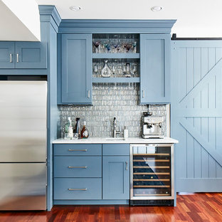 Example of a mid-sized coastal single-wall medium tone wood floor wet bar design in Philadelphia with an undermount sink, shaker cabinets, blue cabinets, metal backsplash and white countertops