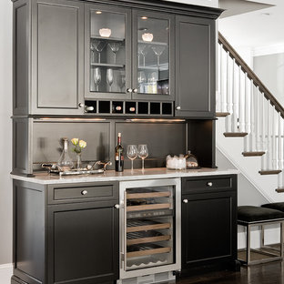 Photo of a traditional home bar in Boston with glass-front cabinets, black cabinets, granite worktops, brown floors and white worktops.