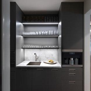Foto di un piccolo angolo bar con lavandino minimalista con lavello sottopiano, ante lisce, ante grigie, top in marmo, paraspruzzi grigio, paraspruzzi in marmo, parquet scuro, pavimento marrone e top grigio