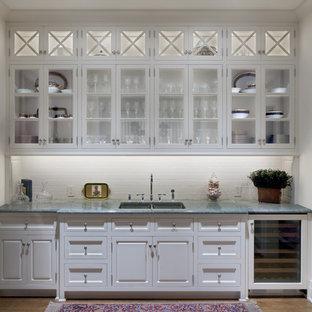 Exempel på en klassisk linjär hemmabar med vask, med en undermonterad diskho, luckor med glaspanel, vita skåp, marmorbänkskiva, vitt stänkskydd och stänkskydd i tunnelbanekakel