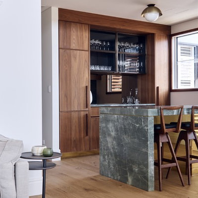 Seated home bar - contemporary galley medium tone wood floor and brown floor seated home bar idea in Sydney with flat-panel cabinets, dark wood cabinets and gray countertops