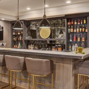 Immagine di un grande bancone bar tradizionale con ante in stile shaker, ante grigie, top in cemento, paraspruzzi multicolore, paraspruzzi con lastra di vetro, top beige, lavello sottopiano, parquet chiaro e pavimento multicolore
