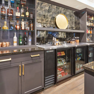 Inspiration for a large transitional u-shaped light wood floor and multicolored floor seated home bar remodel in Chicago with an undermount sink, shaker cabinets, gray cabinets, concrete countertops, multicolored backsplash, glass sheet backsplash and beige countertops