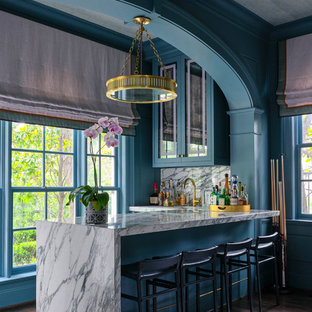 Seated home bar - transitional l-shaped dark wood floor and brown floor seated home bar idea in Dallas with glass-front cabinets, green cabinets, white backsplash and white countertops