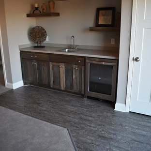 Idée de décoration pour un petit bar de salon avec évier linéaire chalet avec un évier posé, un placard à porte shaker, des portes de placard en bois sombre, un plan de travail en surface solide, une crédence grise, un sol en carrelage de porcelaine et un sol gris.