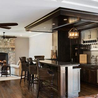 Ispirazione per un grande bancone bar con lavello sottopiano, ante lisce, ante marroni, top in granito, paraspruzzi beige, paraspruzzi con piastrelle in ceramica, parquet scuro, pavimento marrone e top nero