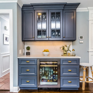 Ispirazione per un angolo bar con lavandino classico di medie dimensioni con ante con riquadro incassato, ante blu, top in marmo, paraspruzzi bianco, paraspruzzi in marmo, parquet scuro e pavimento marrone