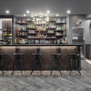 他の地域の広いインダストリアルスタイルのおしゃれな着席型バー (ll型、御影石カウンター、ガラスタイルのキッチンパネル、無垢フローリング、グレーの床、シェーカースタイル扉のキャビネット、濃色木目調キャビネット、黒いキッチンカウンター) の写真