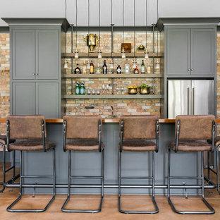 Idee per un bancone bar chic di medie dimensioni con lavello sottopiano, ante in stile shaker, ante grigie, top in legno, paraspruzzi rosso, paraspruzzi in mattoni, pavimento in cemento, pavimento rosso e top marrone