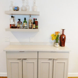 Small traditional single-wall wet bar in Orange County with beaded cabinets, beige cabinets, marble worktops, light hardwood flooring, brown floors and white worktops.
