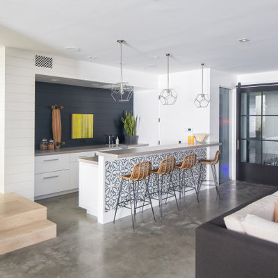 Example of a large beach style single-wall concrete floor and gray floor seated home bar design in Orange County with flat-panel cabinets, white cabinets, blue backsplash, wood backsplash and gray countertops