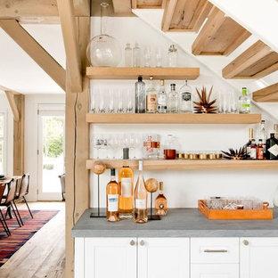 Diseño de bar en casa lineal, de estilo de casa de campo, con puertas de armario blancas, encimera de piedra caliza, salpicadero blanco y armarios estilo shaker