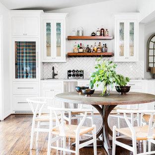 ダラスの広いカントリー風おしゃれなウェット バー (アンダーカウンターシンク、珪岩カウンター、セラミックタイルのキッチンパネル、茶色い床、白いキャビネット、I型、ガラス扉のキャビネット、白いキッチンパネル、グレーのキッチンカウンター、濃色無垢フローリング) の写真