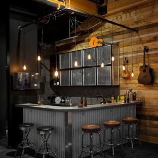 Inspiration for an industrial l-shaped carpeted and black floor home bar remodel in Vancouver with concrete countertops, gray backsplash, porcelain backsplash and gray countertops