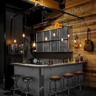 バンクーバーのインダストリアルスタイルのおしゃれなホームバー (コンクリートカウンター、グレーのキッチンパネル、磁器タイルのキッチンパネル、カーペット敷き、L型、黒い床、グレーのキッチンカウンター) の写真